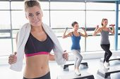 stock photo of step aerobics  - Woman smiling at front of aerobics class in gym - JPG