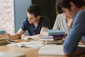 stock photo of homework  - People sitting at the table while doing homework in college library - JPG