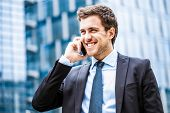 image of commutator  - Portrait of a young businessman talking on the phone - JPG