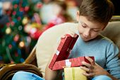 stock photo of pullovers  - Portrait of adorable boy with giftboxes looking into one of them - JPG