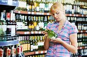 woman choosing bottle of wine in alcohol shopping mall supermarket