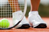 stock photo of sportive  - Legs of sportive girl near the tennis racquet and balls - JPG