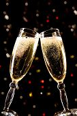 pic of champagne glasses  - Two champagne glasses making toast over holiday background - JPG