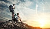 stock photo of mountain-high  - Two tourists with backpacks enjoying sunset on top of a mountain - JPG