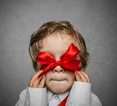 stock photo of pretty-boy  - little boy with a red bow in hand - JPG