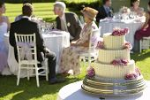 stock photo of cream cake  - Closeup of weeding cake with guests at tables in background - JPG