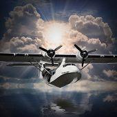 stock photo of hydroplanes  - Vintage seaplane flying against sunset over sea - JPG