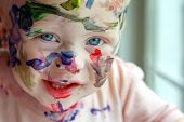 foto of face painting  - a close up photo of a baby boy who has covered his entire face in rainbow colored paint