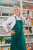 Portrait of happy senior male owner standing against shelves in grocery store