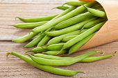 stock photo of bean-pod  - Organic pole beans in paper bag on wooden table - JPG