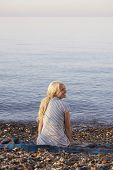 stock photo of herne bay beach  - Rear view of young woman looking away while sitting on blanket at beach - JPG