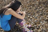 stock photo of herne bay beach  - Full length side view of young woman hugging knees while relaxing at beach - JPG