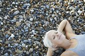 picture of herne bay beach  - High angle view of beautiful young woman with eyes closed lying on pebbles at beach - JPG