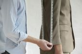 image of tailoring  - Midsection of young male tailor measuring customer - JPG