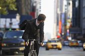 stock photo of car ride  - Young businessman looking over shoulder while riding bicycle on urban street - JPG