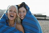 pic of herne bay beach  - Portrait of cheerful young women wrapped in blanket laughing at beach - JPG