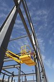 foto of cherry-picker  - Manual worker working from cherry picker on steel framing structure - JPG