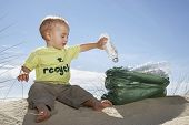 Full length of baby boy collecting empty bottle in plastic bag on beach