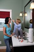 foto of babysitter  - little girl applying makeup to teenage babysitter - JPG