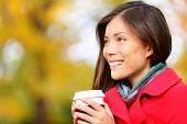 Young woman drinking coffee in Autumn. Fall woman outdoors in autumn forest foliage enjoying hot cof