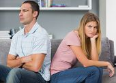 pic of not talking  - Couple sitting back to back after a fight on the couch with woman looking at camera in sitting room at home - JPG