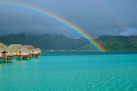 stock photo of french polynesia  - Double rainbow on top of Polynesia over-water luxury bungalows