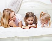 Mother And Her Daughters Reading Bed Time Story Book