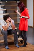 picture of moaning  - Angry woman standing by bored husband and moaning - JPG