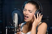 picture of recording studio  - Portrait of young woman recording a song in a professional studio - JPG