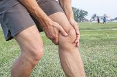 picture of hamstring  - Closeup of athletic Caucasian man holding his painful knee on soccer field - JPG