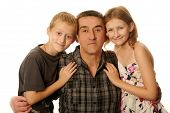 foto of ten years old  - Twelve year old daughter and ten year old son having fun hugging father with love isolated on white background - JPG