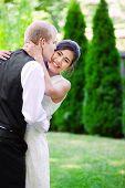 pic of biracial  - Caucasian groom lovingly kissing his biracial bride on cheek - JPG