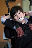 image of biracial  - Handsome disabled eight year old biracial boy smiling and relaxing in wheelchair - JPG