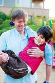 picture of biracial  - Caucasian father carrying biracial disabled son on playground - JPG