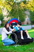 stock photo of biracial  - Biracial older sister playing outdoors with disabled little brother in wheelchair - JPG