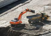 foto of excavator  - Excavator loading dumper truck tipper in sandpit in highway construction site  - JPG
