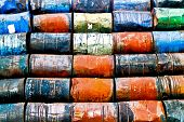 stock photo of staples  - Horizontal staple of colorful used oil drums on a storage site - JPG