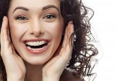 foto of studio  - closeup portrait of attractive  caucasian smiling woman brunette isolated on white studio shot lips toothy smile face hair head and shoulders looking at camera tooth - JPG