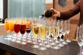 pic of bartender  - Bartender is pouring sparkling wine in glasses - JPG