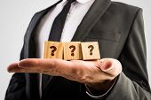 stock photo of cube  - Businessman holding three wooden cubes displaying question marks - JPG