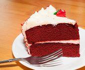 picture of red velvet cake  - Red velvet cake with white frosting on a plate - JPG