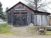 pic of blacksmith shop  - a vintage black smith shop sits alongside a road.
