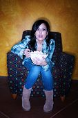 pic of watching movie  - Hispanic woman with popcorn watching television - JPG