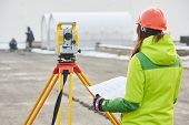 stock photo of geodesic  - female surveyor worker working with theodolite transit equipment at road construction site outdoors - JPG