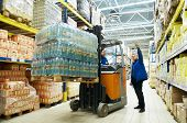foto of forklift  - worker and manager distributing goods in a warehouse with forklift truck loader - JPG