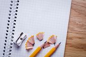 pic of pencils  - Two sharpened pencil pencil sharpener and unfolded notebook on wooden office desk - JPG