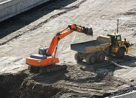 foto of dumper  - Excavator loading dumper truck tipper in sandpit in highway construction site  - JPG