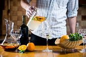 stock photo of sangria  - Man pours white homemade sangria with fruit pieces in a glass - JPG