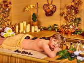 stock photo of stone-therapy  - Woman getting stone therapy massage in bamboo spa - JPG