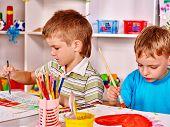 foto of nursery school child  - Children painting at easel in school - JPG